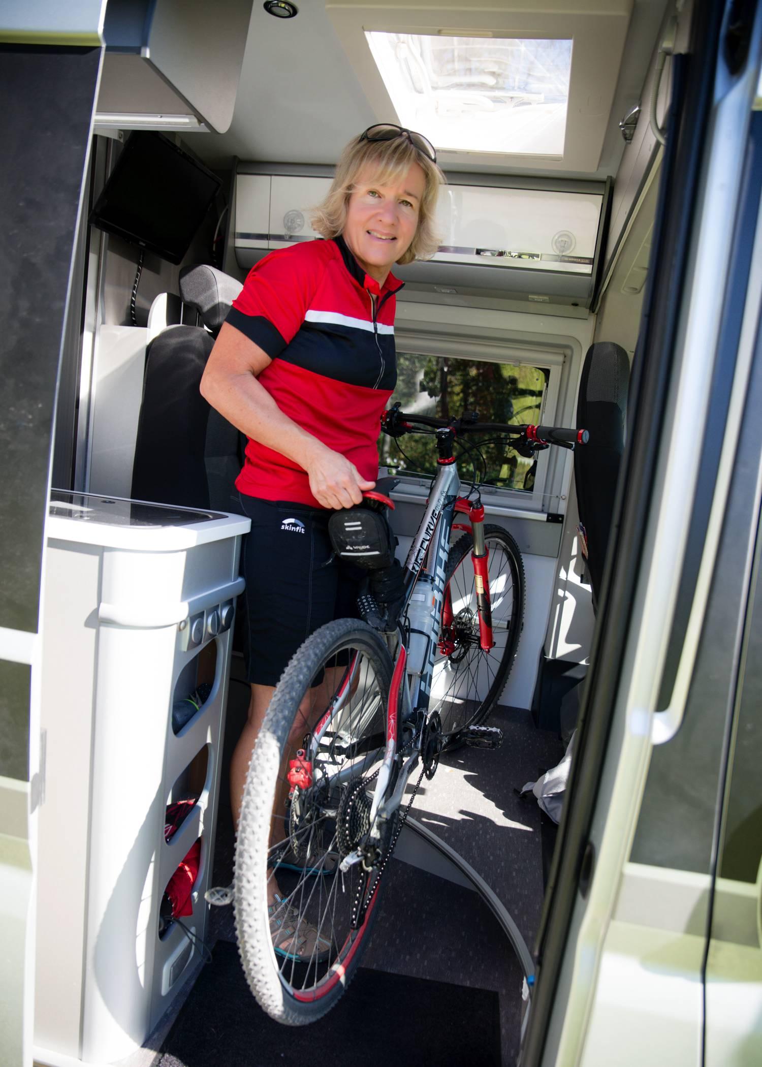 Annett hebt ihr Fahrrad in den Campingbus
