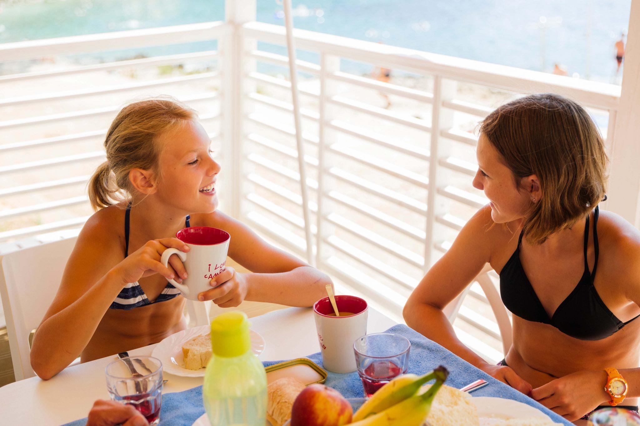 Die beiden Geschwister genießen den Campingurlaub, Frühstück auf der Terrasse