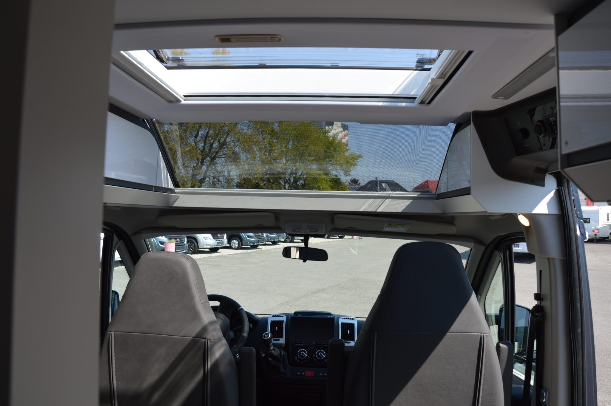 Wohnmobil mit Panoramafenster über dem Fahrerhaus.