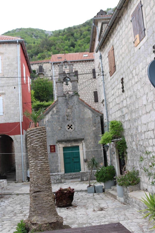 Alte Häuser, Kirchen und eine Strandpromenade in Perast.